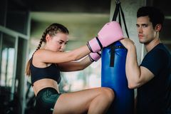 Fit beautiful woman boxer hitting a huge punching bag exercise class in a gym. Boxer woman making direct hit dynamic movement. Fit beautiful women boxer hitting royalty free stock image