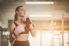 Fit beautiful woman boxer hitting a huge punching bag exercise class in a gym. Boxer woman making direct hit dynamic movement. Healthy, sports, lifestyle royalty free stock image