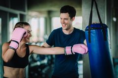 Fit beautiful woman boxer hitting a huge punching bag exercise class in a gym. Boxer woman making direct hit dynamic movement. Fit beautiful women boxer hitting stock photo