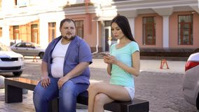 Fit beautiful woman ignoring fat man sitting on bench, sad unconfident bachelor. Fit beautiful women ignoring fat men sitting on bench, sad unconfident bachelor royalty free stock photography