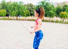 Fit beautiful woman with jumping rope in a park stock photo