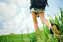Fit and beautiful woman`s legs with backpack walking across green field. Beautiful woman`s legs with backpack walking across green field Stock Photography