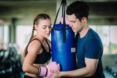 Fit beautiful woman boxer hitting a huge punching bag exercise class in a gym. Boxer woman making direct hit dynamic movement. Fit beautiful women boxer hitting stock photos