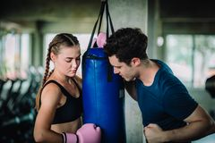 Fit beautiful woman boxer hitting a huge punching bag exercise class in a gym. Boxer woman making direct hit dynamic movement. Fit beautiful women boxer hitting stock image