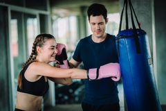 Fit beautiful woman boxer hitting a huge punching bag exercise class in a gym. Boxer woman making direct hit dynamic movement. Fit beautiful women boxer hitting royalty free stock photography