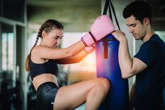 Fit beautiful woman boxer hitting a huge punching bag exercise class in a gym. Boxer woman making direct hit dynamic movement. Fit beautiful women boxer hitting royalty free stock images