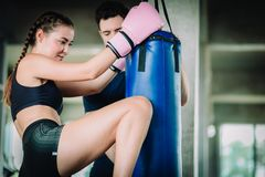 Fit beautiful woman boxer hitting a huge punching bag exercise class in a gym. Boxer woman making direct hit dynamic movement. Fit beautiful women boxer hitting royalty free stock photos