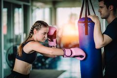 Fit beautiful woman boxer hitting a huge punching bag exercise class in a gym. Boxer woman making direct hit dynamic movement. Fit beautiful women boxer hitting royalty free stock photo