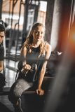 Fit beautiful young woman caucasian attractive fitness woman exercise with dumbbell by trainer in gym. royalty free stock photography