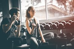 Fit beautiful young woman caucasian attractive fitness woman exercise with dumbbell by trainer in gym. stock photos