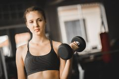 Fit beautiful young woman caucasian posing at the camera in sportswear. Young woman holding dumbbell. During an exercise class in a gym. Healthy sports royalty free stock photo