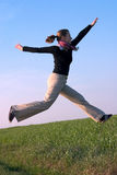 Fit beautiful young woman jumping into the sky. Young woman jumping Stock Photography