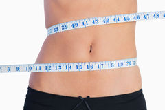 Fit belly surrounded by measuring tape Royalty Free Stock Photography