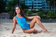 Fit bikini model posing in blue swimwear at paradise beach resort. Royalty Free Stock Images
