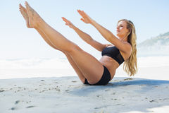 Fit blonde in core balance pilates pose on the beach Stock Photography