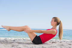 Fit blonde doing pilates core exercise. On the beach royalty free stock image