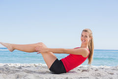 Fit blonde doing pilates core exercise smiling at camera. On the beach royalty free stock photography