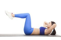 Fit blonde doing pilates core exercise in studio. Fit blonde doing pilates core exercise on yoga pad in studio stock photo