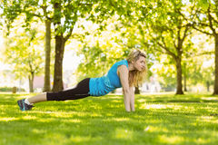 Fit blonde doing push ups in the park Royalty Free Stock Photos