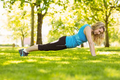 Fit blonde doing push ups in the park Stock Photography