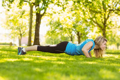 Fit blonde doing push ups in the park Royalty Free Stock Photo