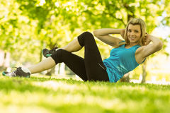 Fit blonde doing sit ups in the park Stock Photos