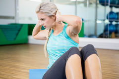 Fit blonde doing sitting up on mat Royalty Free Stock Photography