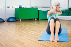 Fit blonde doing sitting up on mat Stock Photos