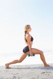 Fit blonde doing weighted lunges on the beach Stock Images
