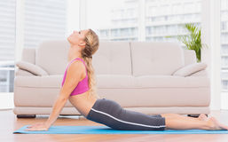 Fit blonde doing yoga on exercise mat Royalty Free Stock Images