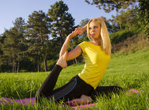 Fit blonde doing yoga pose in nature. Fit beautiful, blonde doing yoga pigeon pose in nature Stock Photos