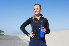 Fit blonde holding bottle on the pier Royalty Free Stock Image