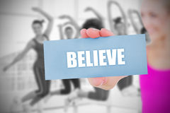 Fit blonde holding card saying believe Stock Photos