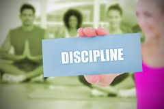 Fit blonde holding card saying discipline Stock Photo