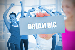 Fit blonde holding card saying dream big Stock Image