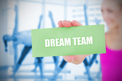 Fit blonde holding card saying dream team Stock Image