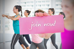 Fit blonde holding card saying join now Royalty Free Stock Photo