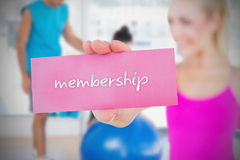 Fit blonde holding card saying membership Royalty Free Stock Images