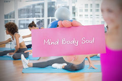 Fit blonde holding card saying mind body soul. Against yoga class in gym royalty free stock photos