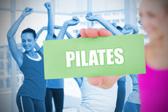 Fit blonde holding card saying pilates Royalty Free Stock Photography