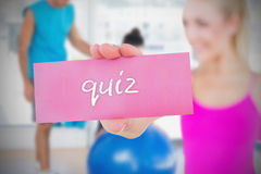 Fit blonde holding card saying quiz Stock Images