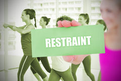 Fit blonde holding card saying restraint. Against zumba class in gym Royalty Free Stock Photos