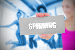 Fit blonde holding card saying spinning Royalty Free Stock Photography