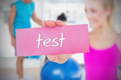 Fit blonde holding card saying test Stock Photos