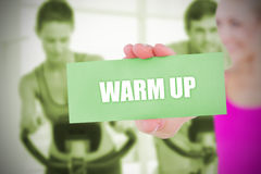 Fit blonde holding card saying warm up Royalty Free Stock Photography