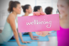 Fit blonde holding card saying wellbeing Royalty Free Stock Image