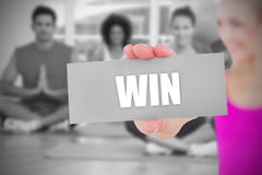 Fit blonde holding card saying win Royalty Free Stock Photography