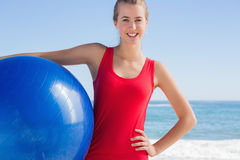 Fit blonde holding exercise ball looking at camera Stock Photos