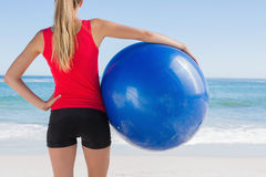 Fit blonde holding exercise ball looking at sea Royalty Free Stock Images