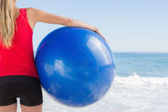 Fit blonde holding exercise ball looking at waves Stock Photo